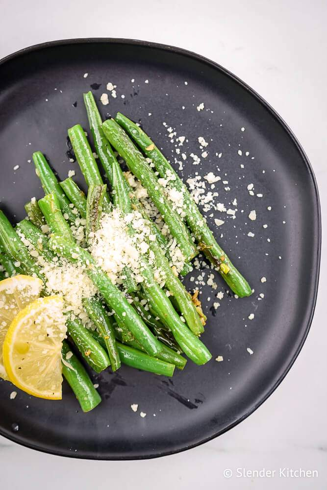 Parmesan roasted green beans with lemon slices on a plate with a napkin.
