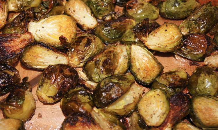 Roastied brussels sprouts on a baking sheet with brown edges.