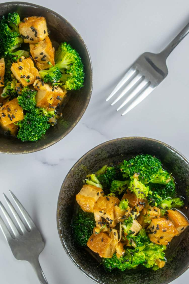 Sesame tofu with sesame seeds and broccoli in two black bowls with forks.