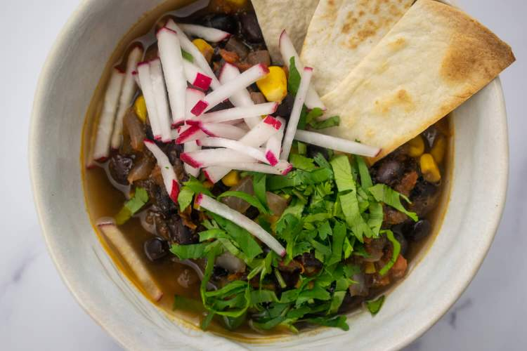 Bowl of tortilla soup with beans and corn with tortilla strips and cilantro.