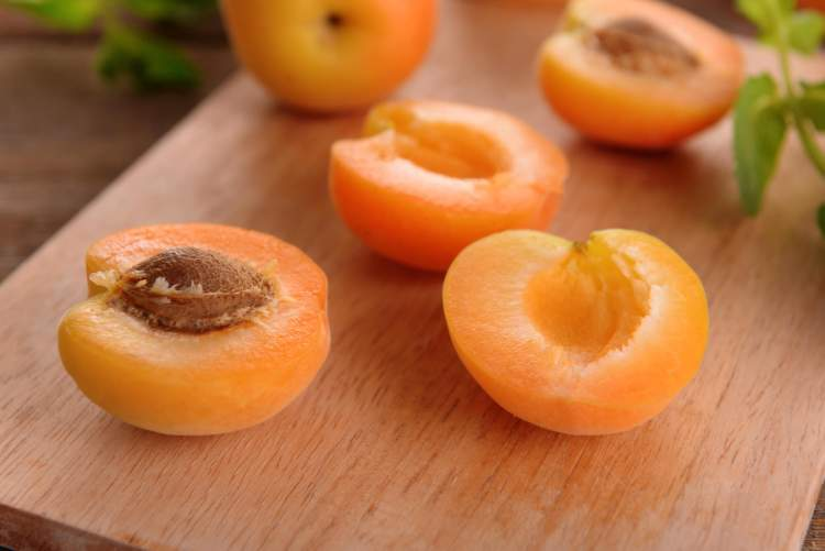 Fresh apricots on a cutting board before being used for an apricot crumble recipe.