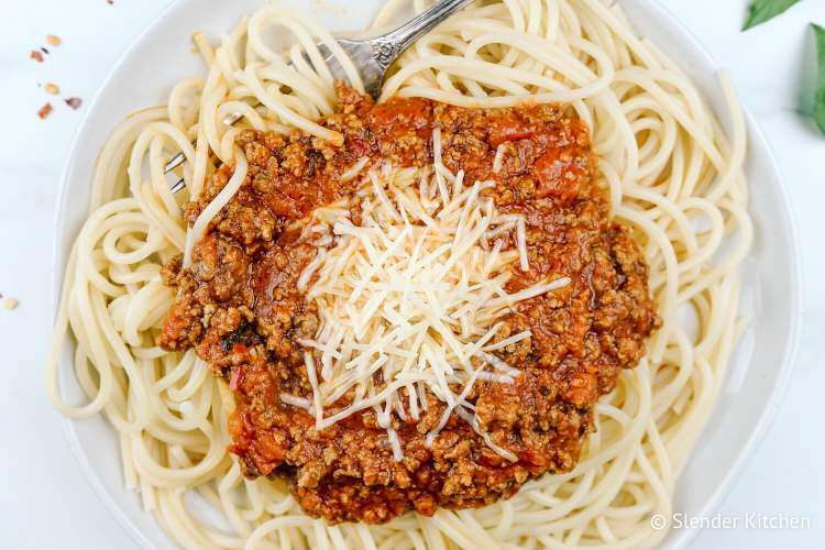 Arrabiata sauce with pasta on a plate with red pepper flakes and cheese.