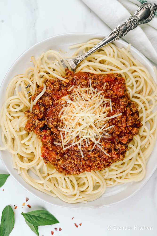 Spaghetti Arrabiata on a white plate with Parmesan cheese and basil.