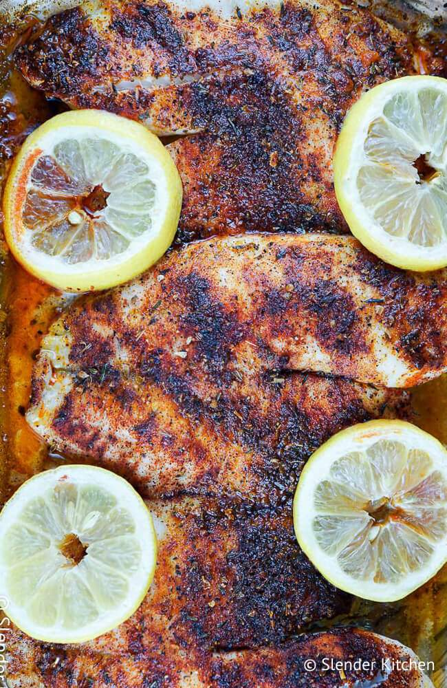 Baked blackened tilapia in a glass dish with lemon slices and blackening spices.