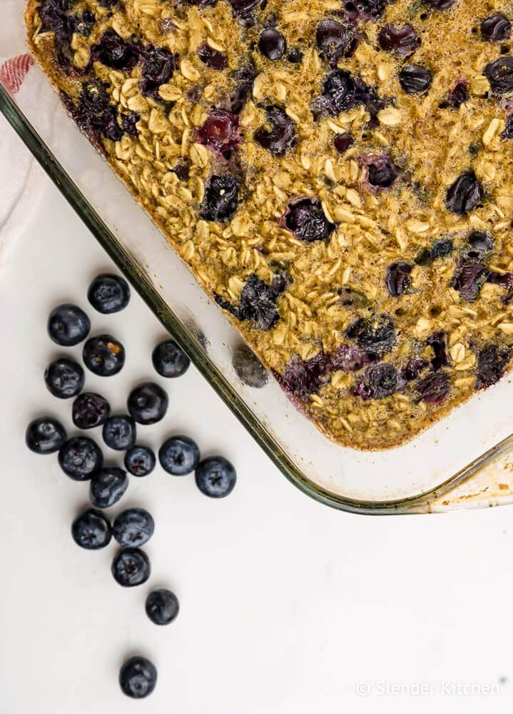 Baked blueberry oatmeal in a glass dish with blueberries on the side.