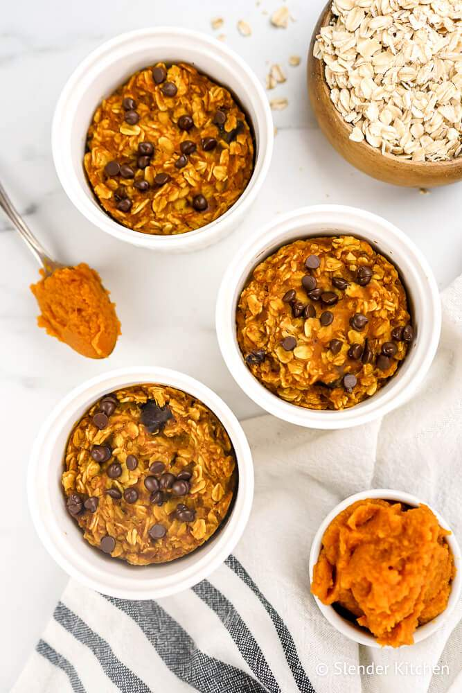 Baked pumpkin oatmeal with chocolate chips in white baking dishes.