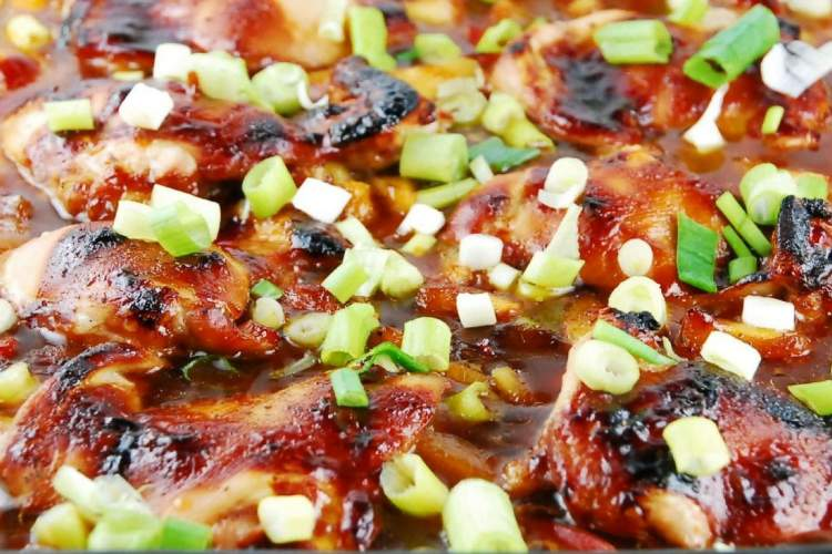 Baked teriyaki chicken in a glass dish with green onions.