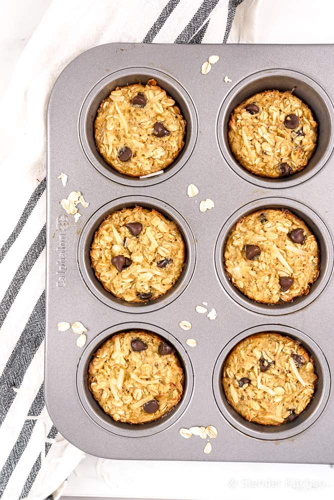 Baked oatmeal muffins with bananas, shredded coconut, and chocolate chips in a muffin tin.