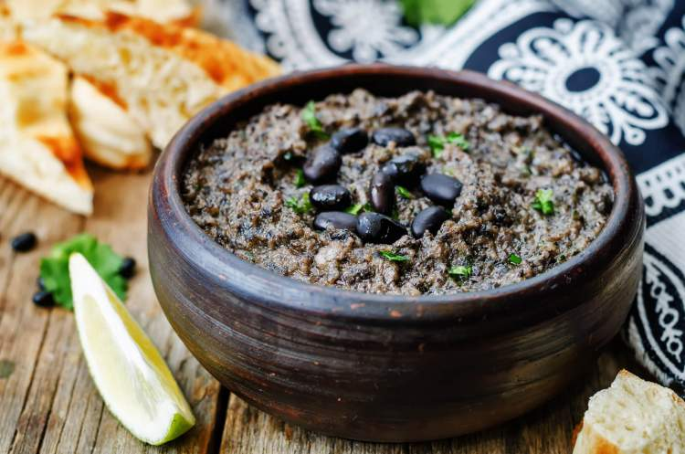 Black bean hummus with cilantro and limes on a wooden board.
