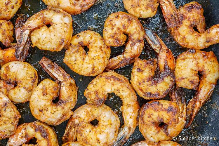 Blackened shrimp with a homemade spice rub in a black skillet.