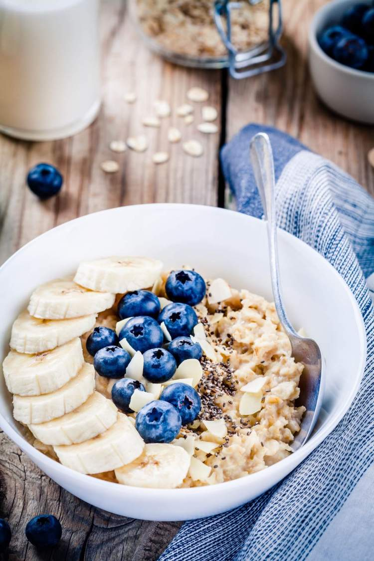 Chai Overnight oats with blueberries and bananas in a bowl with spoon.