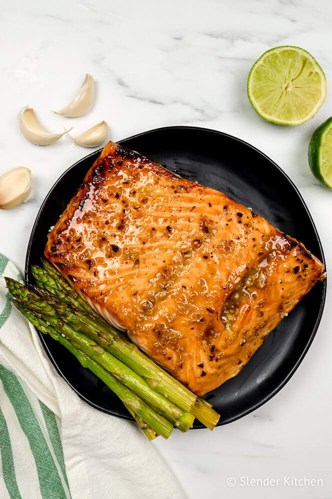 Broiled salmon on a black plate with asparagus and lime.