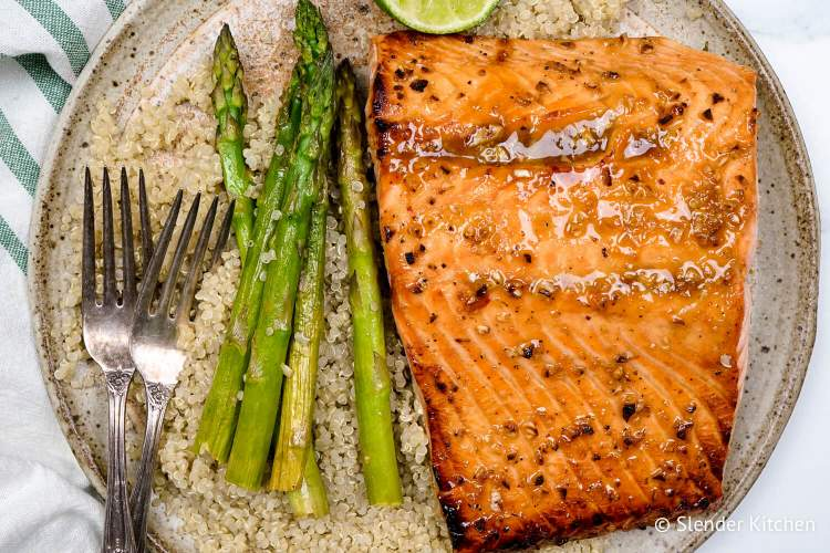 Broiled salmon on quinoa with asparagus on a ceramic plate.