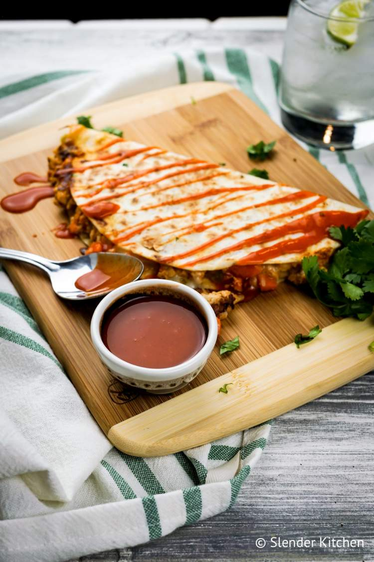 Buffalo Chicken Quesadillas on a cutting board with blurred background.