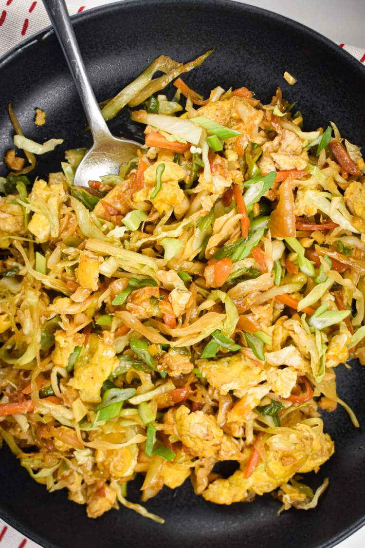Cabbage rice that is fried with carrots, onions, garlic, ginger, and soy sauce on a plate.