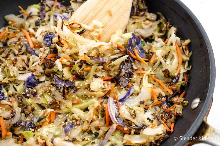 Stir fry cabbage in a skillet with sesame seeds.