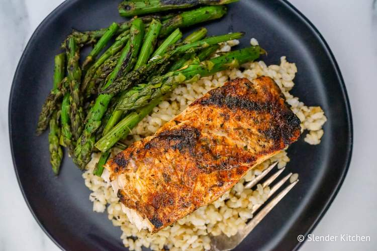 Broiled Cajun Salmon on a black plate with rice and asparagus on a white linen napkin.