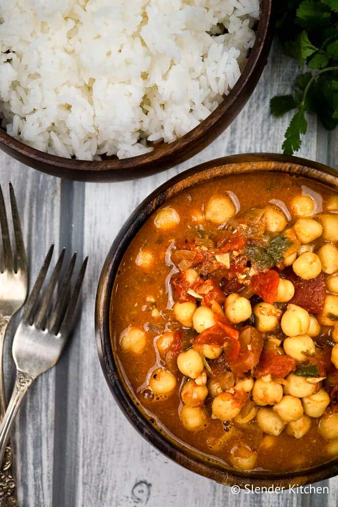Chana Masala recipe in a wooden bowl with cilantro and white rice.
