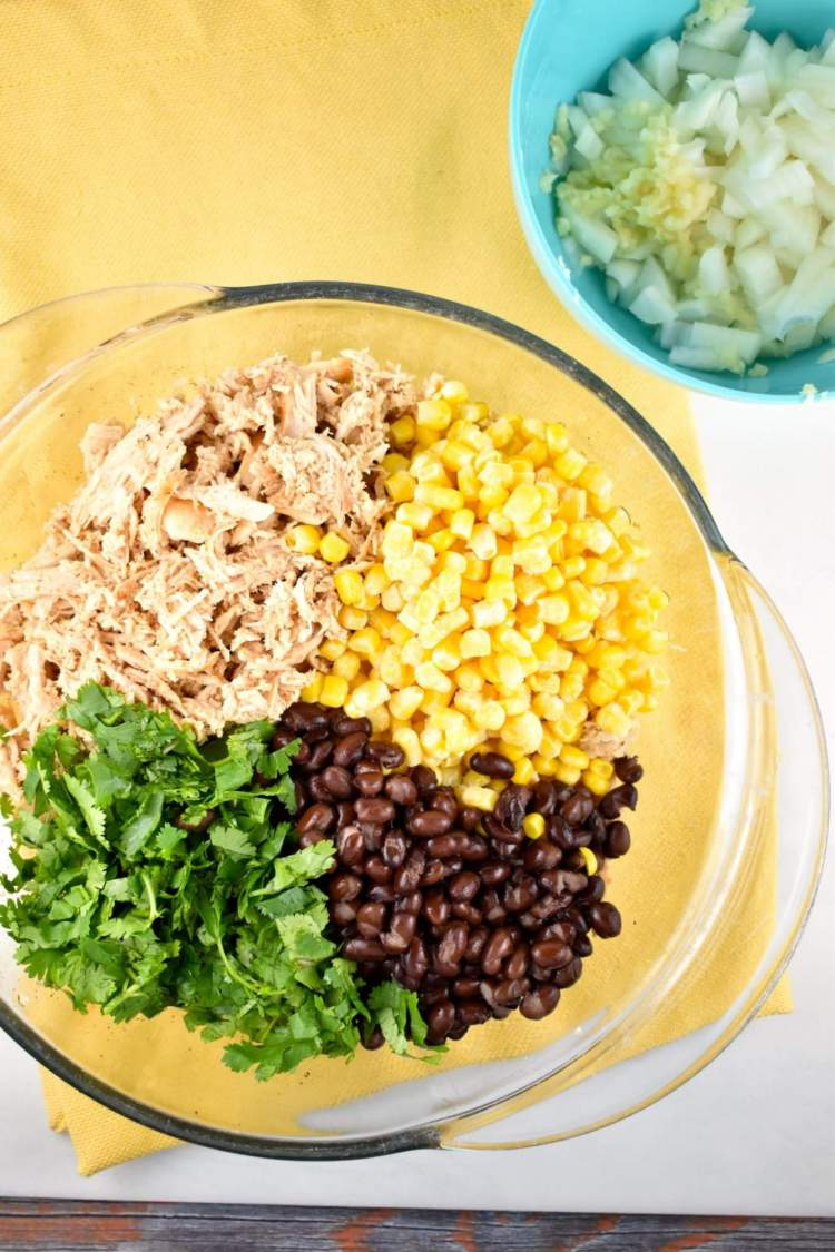 Chicken, black beans, cilantro, and corn in a glass bowl with a yellow napkin.