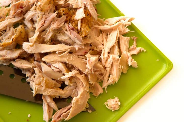 Shredded chicken on a cutting board for chicken enchilada casserole.