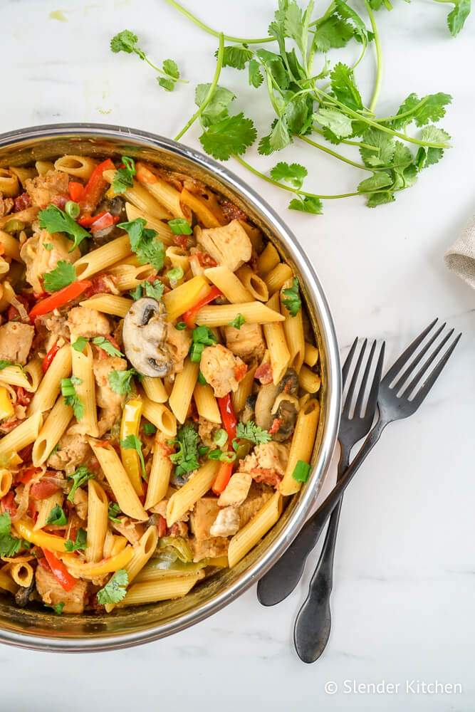Chicken Fajita Pasta in a pan with peppers, onions, tomatoes, and mushrooms with cilantro on the side.