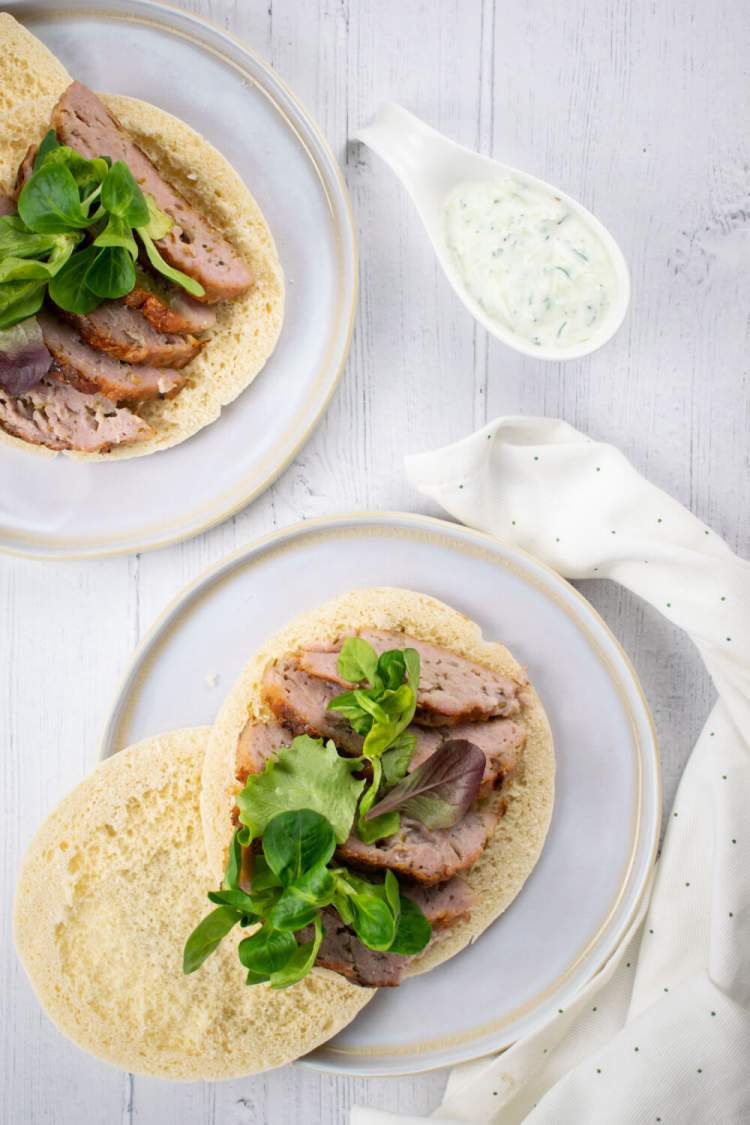 Chicken gyro meat sliced thin on pita bread with lettuce and tzatziki on the side.