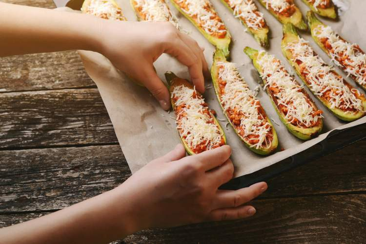 Chicken parmesan zucchini boats with a hand sprinkling cheese on top.