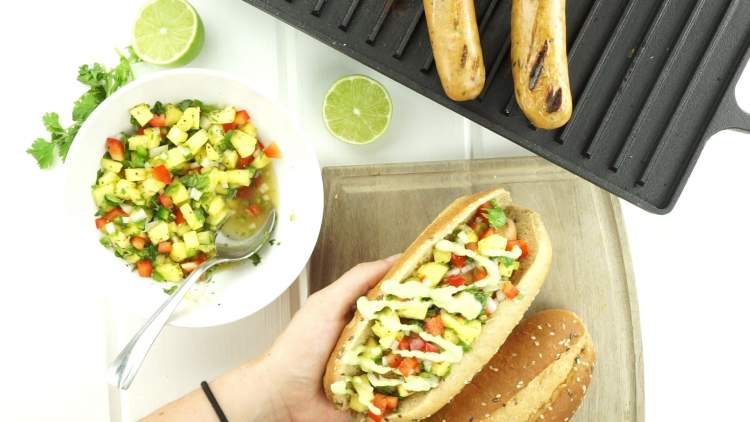 Pineapple Chicken Sausages on the grill with salsa and limes.