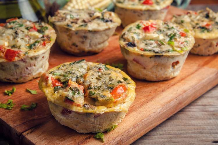 Omelet muffins with veggies on a cutting board with blurred kitchen background.