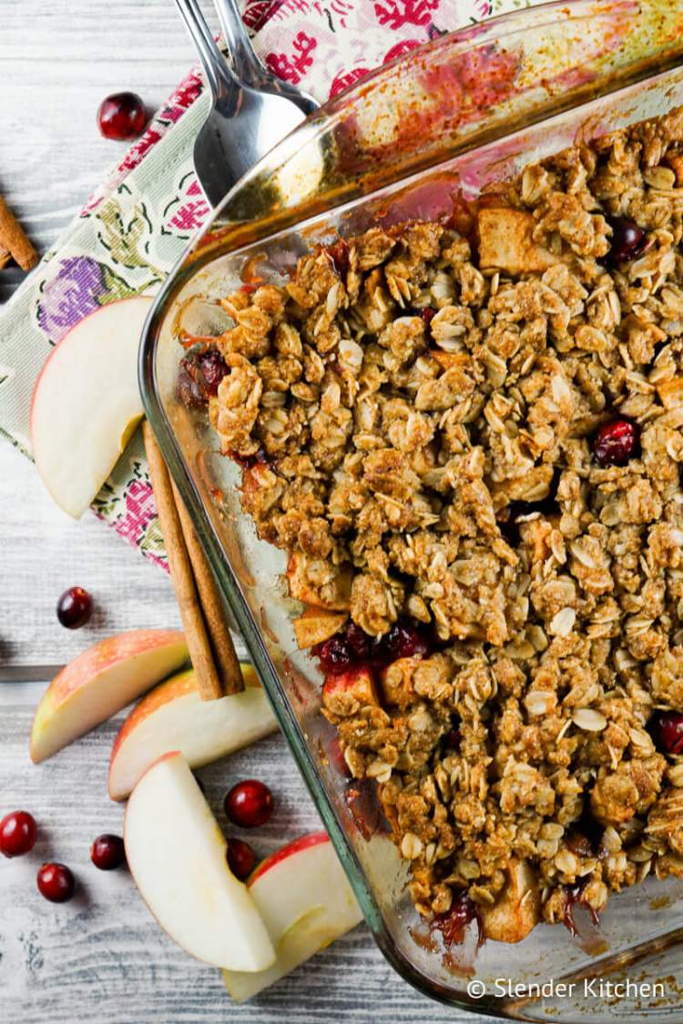Apple Cranberry Baked Oatmeal in a glass baking dish with two spoons.