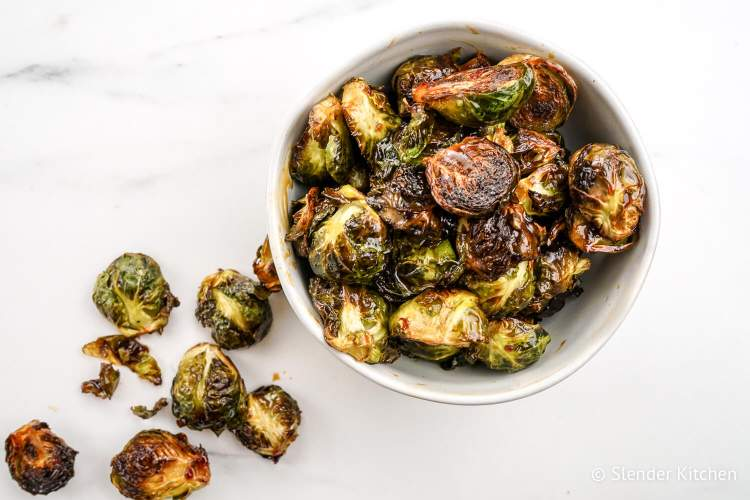 Roasted Asian Brussel sprouts in a bowl with a soy honey sauce.
