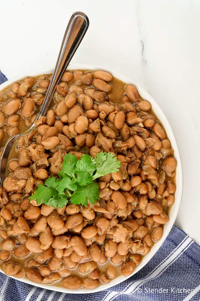 Slow cooker pinto beans in a bowl with a spoon and cilantro.