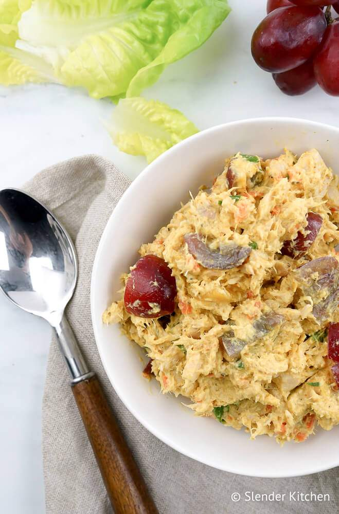 Curried tuna salad in a bowl with red grapes and lettuce on the side.
