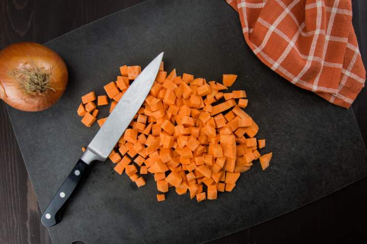 Diced sweet potatoes with an onion and a knife