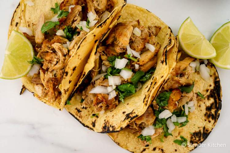 Easy carnitas in three tacos with onion, limes, and cilantro.
