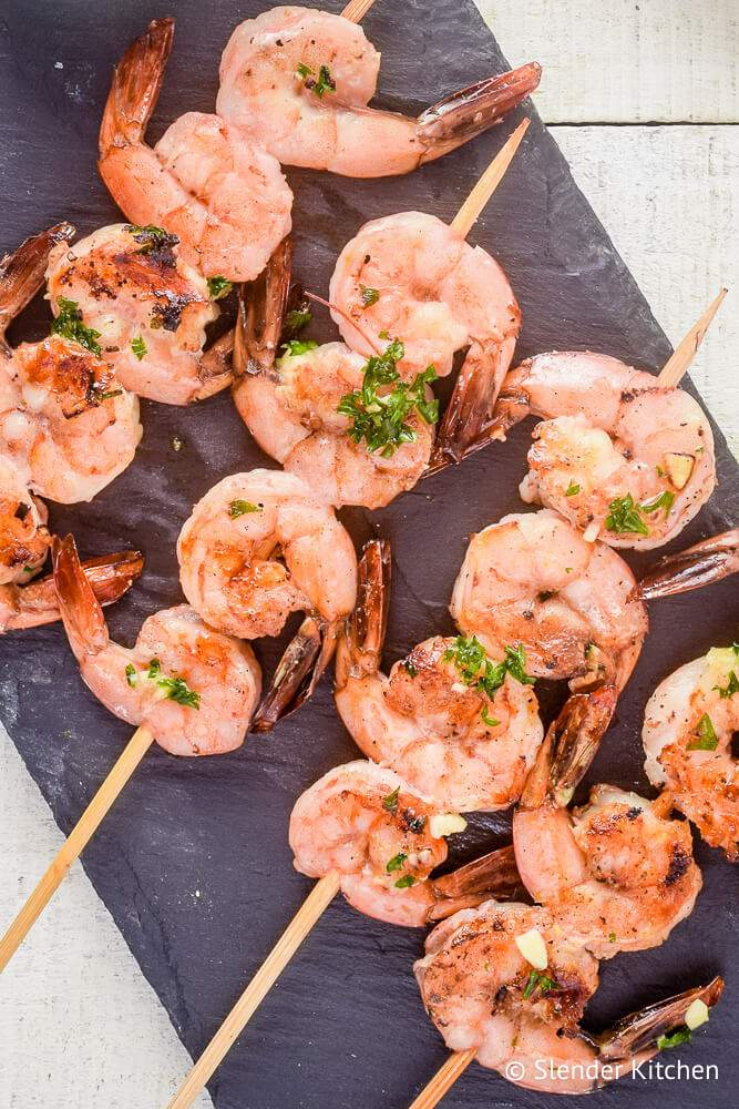 Shrimp kabobs cooked on skewers with lemon, garlic, and parsley.