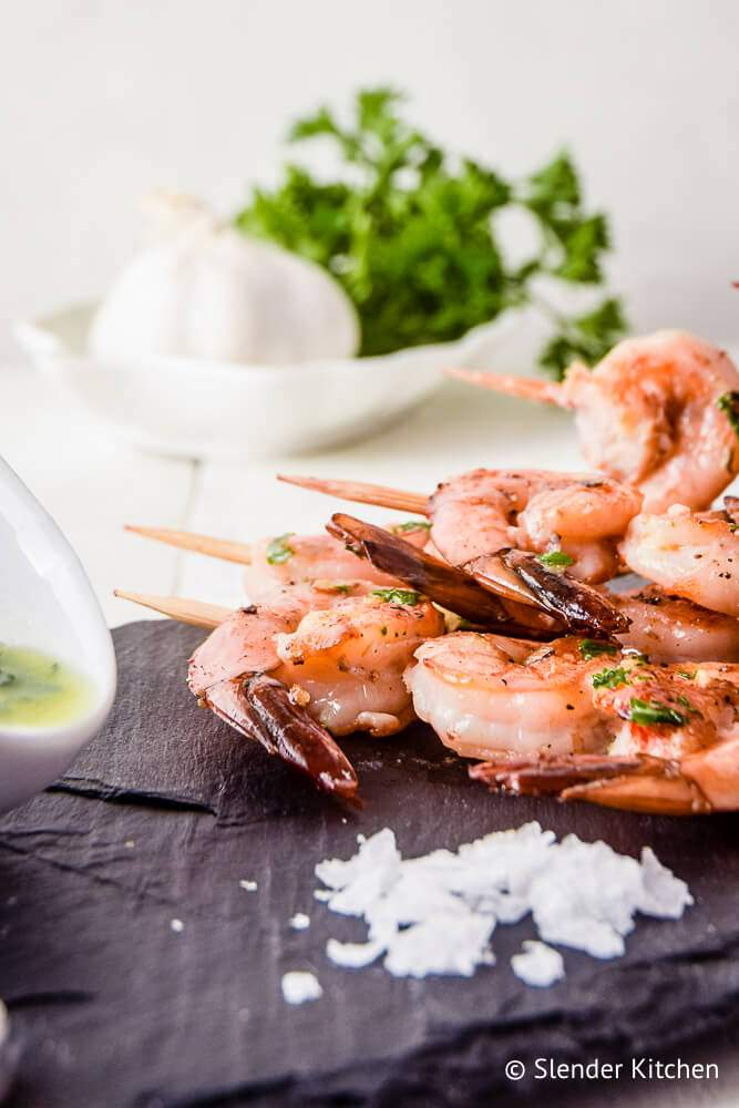 Shrimp kabobs with lemon, garlic, and parsley on skewers.