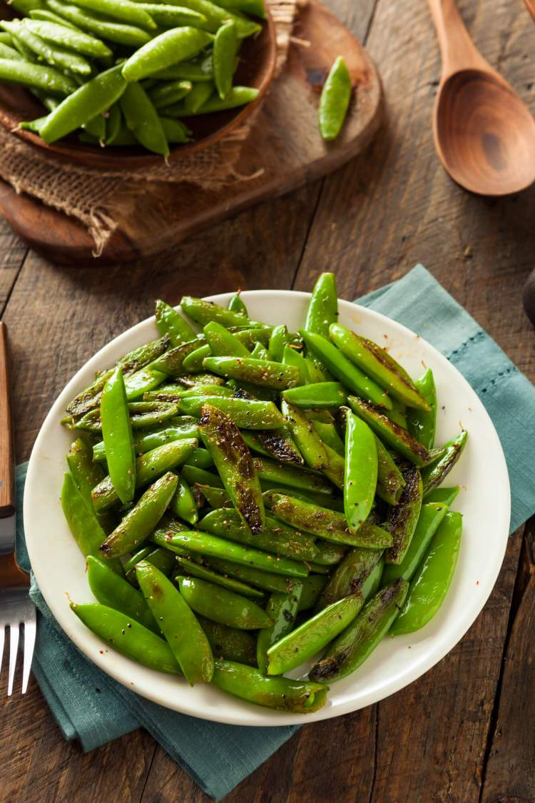 Snap pea recipe cooked on a wooded plate with a napkin.