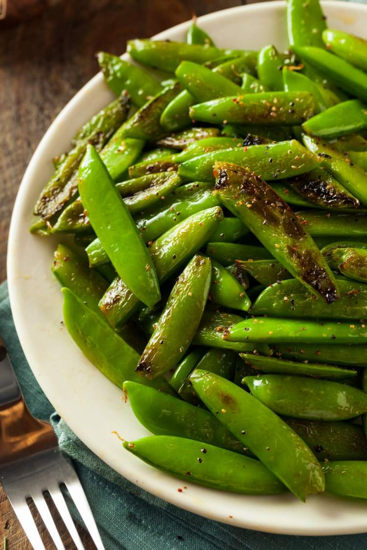 Sauteed sugar snap peas on a plate that are lightly browned.
