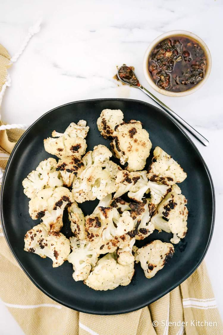 Grilled cauliflower on a black plate with chimichurri.