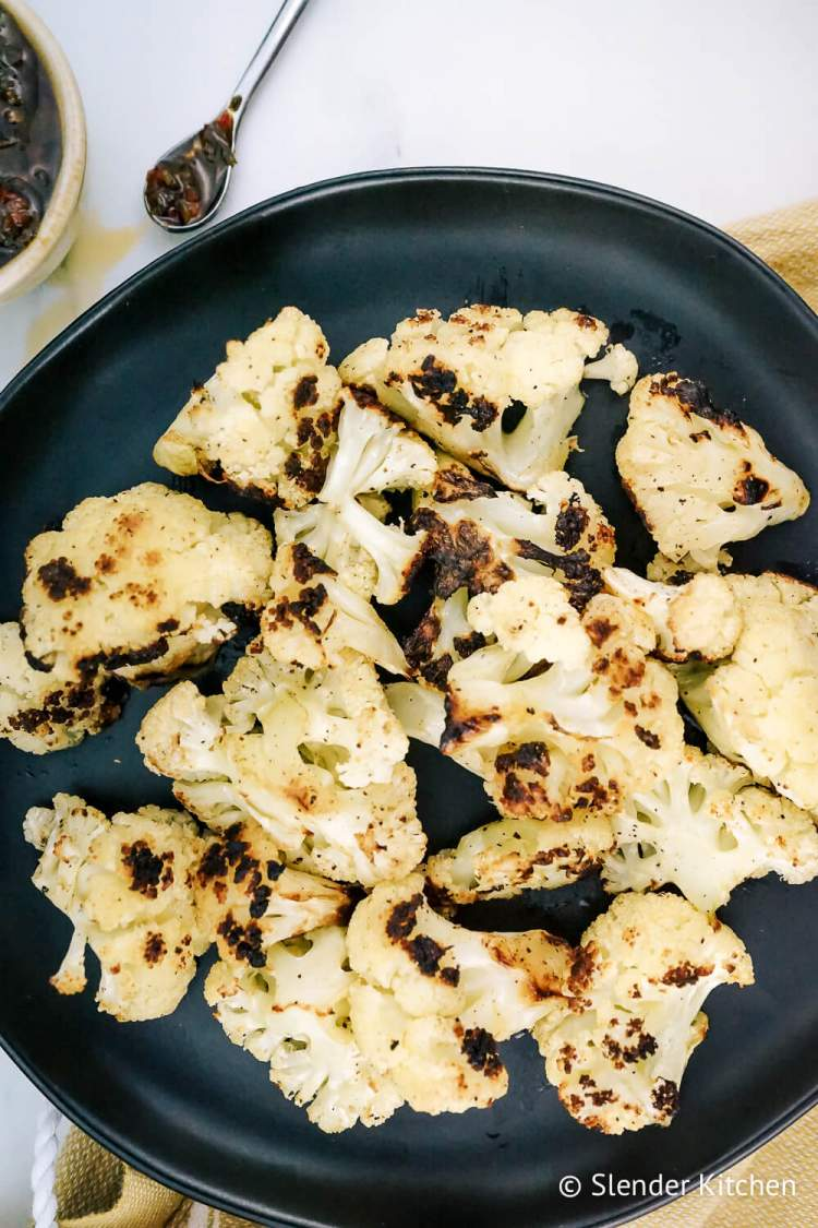 Grilling cauliflower on a white cutting board with a bowl of herbs in olive oil.