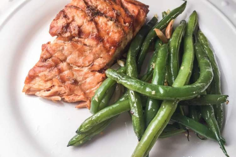 Grilled salmon with green beans on a white plate.