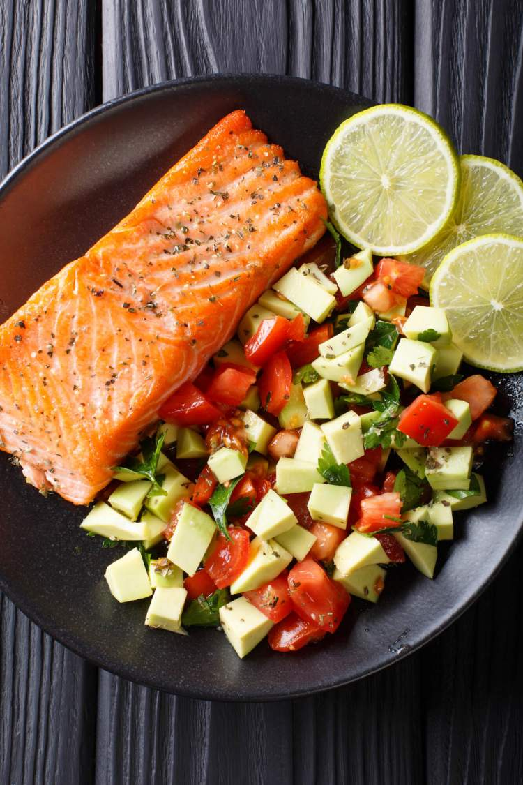Grilled salmon with honey and lime with an avocado salad on a black plate.