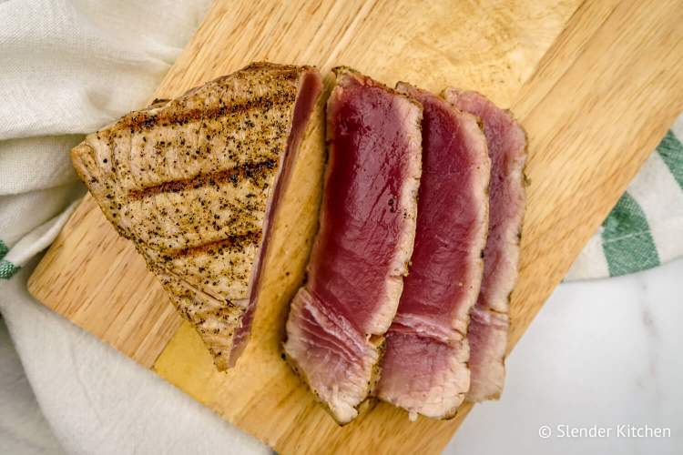 Easy grilled tuna on a wooden cutting board in small slices.