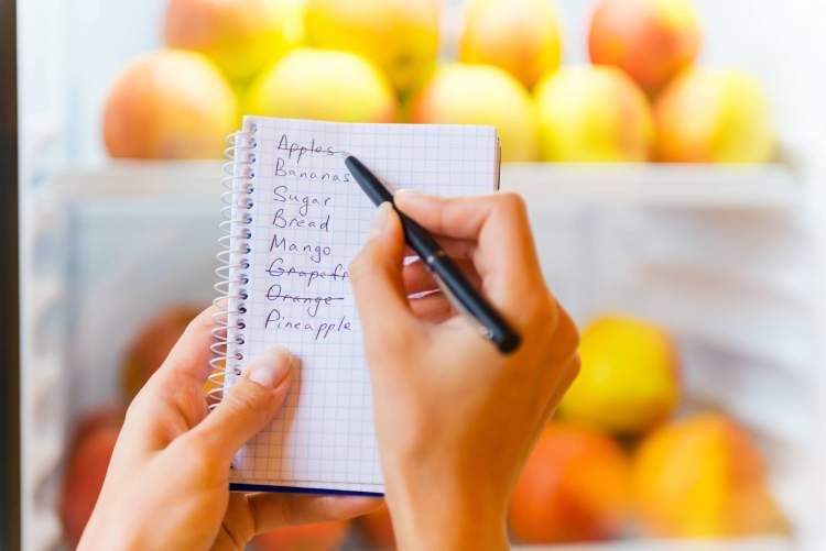 Shopping list with pencil and fridge in the background.