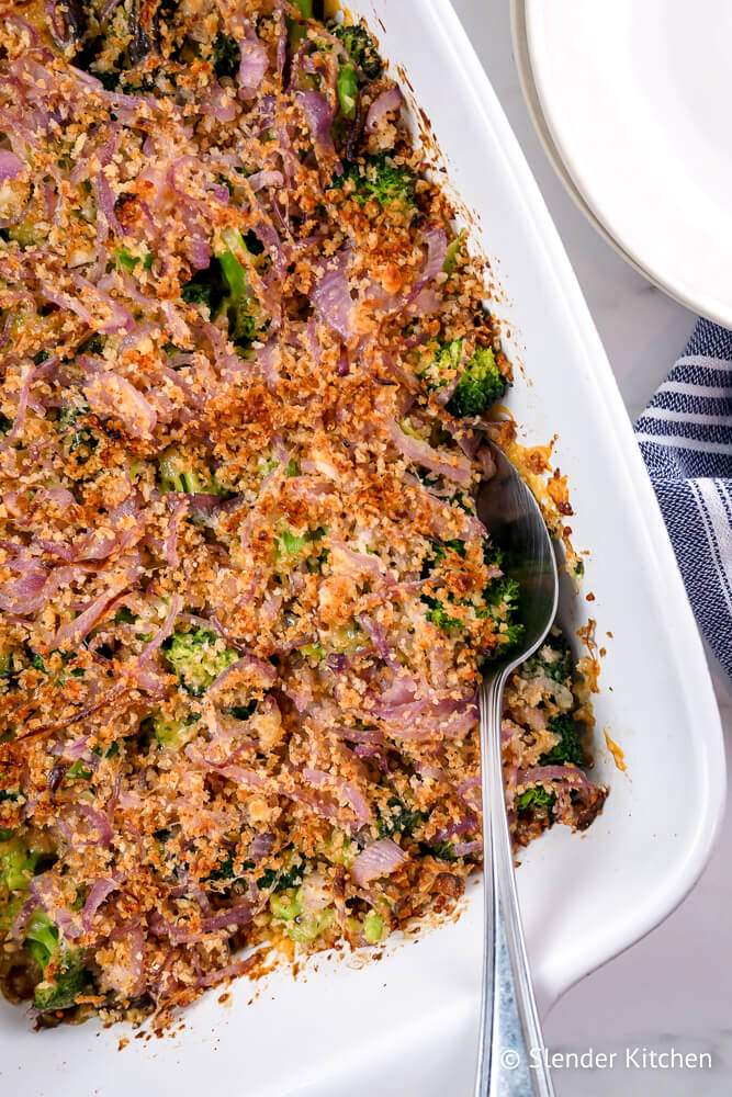 Broccoli casserole with crispy red onion, breadcrumbs, and mushrooms in a ceramic dish.