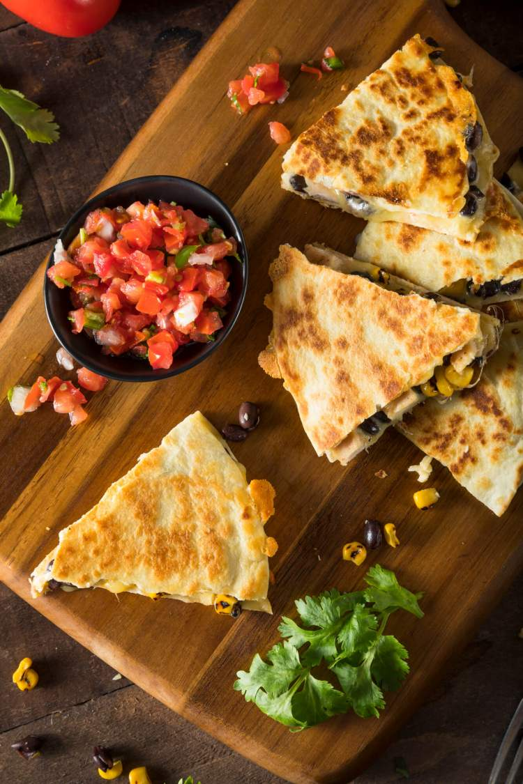 Healthy Chicken Quesadillas cut into pieces with tomatoes and cilantro.