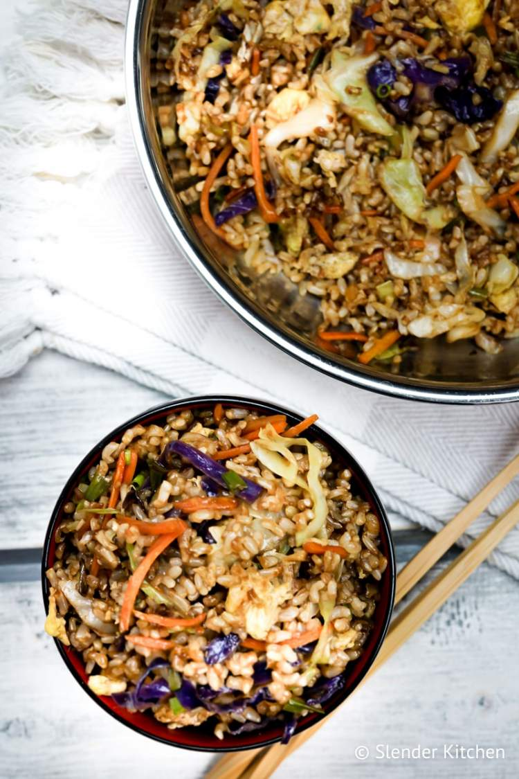 Healthy fried rice served in a small bowl with fresh green onions and chopsticks.