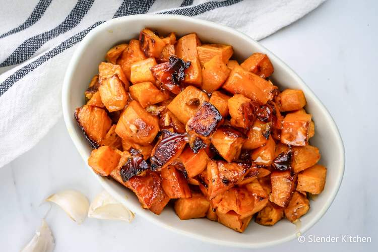 Honey roasted sweet potatoes with garlic in a dish with caramelized browned edges.