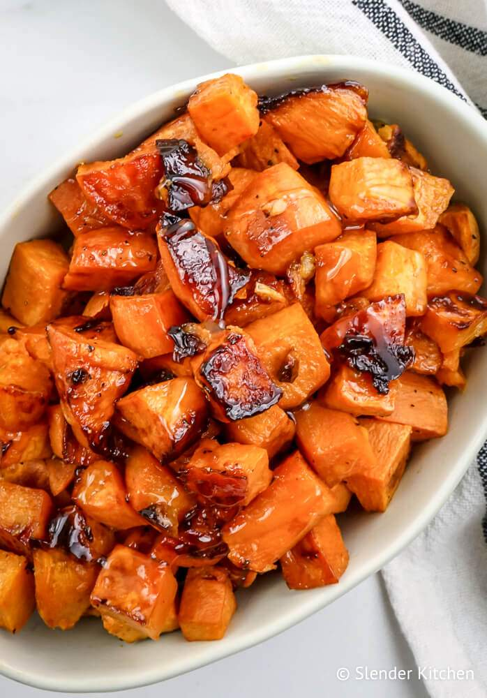 Roasted sweet potatoes with honey in a dish with a white napkin on the side.